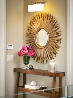 A large sunburst mirror adds a burst of energy and style to this neutral entryway. Hung above a rustic console table, the mirror adds a warm contemporary touch to the overall design.