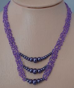 Purple Pride   This is a quick and easy necklace to make. I combined RAW and net weave for the straps of the necklace which gives it a firm base and easy to make.   Project Type: Bead Stitch: Net and RAW Beads Used: Size 8 seed beads and 4 different sized pearls. Approx Finished Size: 18 Pages to Print: 4