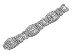Designed as a series of open work geometric links set with circular-, single-cut and baguette diamonds ca 1930