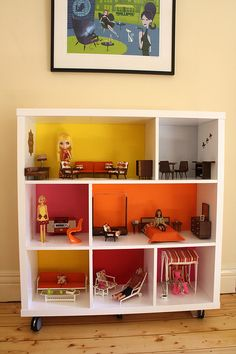 Could totally use this in a classroom!  What a cute idea to use a book shelf for a doll house! You could even paint the backs of the shelf with different scenes to use for toy storage and play - like a stack of books painted on the back where the books go, a race track scene where the cars belong, etc.