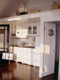 Coastal Living; Designers decorated this cottage around a central, nautical theme. They added subtle accents, like a porthole window in the                            kitchen door, and seaworthy knickknacks along a high ledge. The result? A yachty interior that makes you feel like you're                            on the deck of a boat.