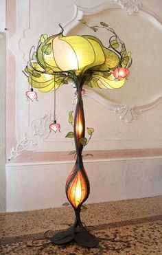 Art Nouveau: Flower Lamp. Very curvy, asymmetrical and unbalanced. Almost looks like it could topple over. The lamp stand has decorative feet that resemble roots spreading across the floor. The extreme detail in the vines spreading above the lamp and flowers hanging off. Delicate feminine colours of soft greens and pinks. The plaster mouldings on the wall behind is also asymmetrical and decorative. No surface is left untouched,