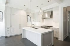 L shaped kitchen features white shaker cabinets paired with white quartz countertops and backsplash.