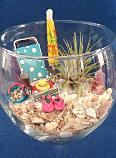 """Beach Wine Glass   Small air plant surrounded by a beach chair, umbrella, flip flops, bucket w/ seashells on white sand.   8"""" wine glass is adorned with a colorful flip-flop  wine charm.    Jody's Boutique Gardens - Bellevue, NE"""