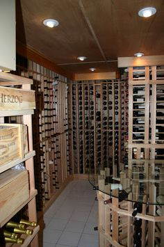 Large wine room with modern accents, custom made glass top table with additional wine storage. longislandwinecellars.com
