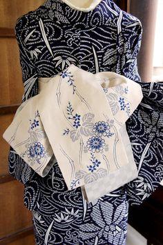 白に近いベージュがかった淡いグレーの地に、深みのある青で、しなやかにしなる細竹のような立涌縞と菊花や花桐の草花模様が織り出された、凛と美しい半幅帯です。
