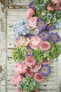 Shabby chic flowers on rustic shutters beautiful for staging behind the bride…