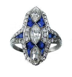 Diamond and sapphire panel cluster ring, three central marquise diamonds with calibrй sapphires between, diamond line border, sapphire and diamond shoulders. Art Deco or Art Deco style