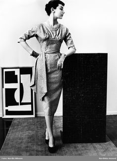 1955. Modell i klänning i jacquardvävd helsiden, handskar, pumps och halsband. Konst i bakgrunden. Foto: Nordin Nilsson