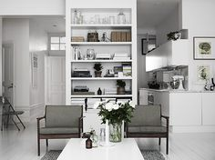 Black and white needn't look cold - here, the white backdrop draws attention to the details and objects. The living room and kitchen are separated by a wall of shelves. Photo by Pia Ulin.