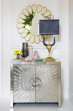 Simon Doonan - A console topped with a table lamp, vases, and decorative objets; wall art above