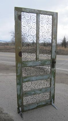 Spirals of Barbed Wire In Upcycled Door. This would make an awesome trellis! OH YES IT WOULD...YET HATE TO OBSCURE THE ART WORK, THAT BEING THE WIRE WORK...THOUGHTS FLYING!