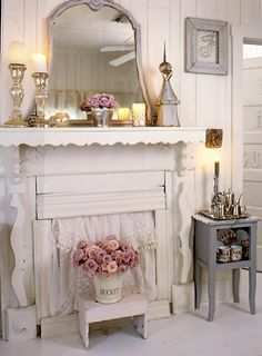 Shabby chic cottage, soft grays and pinks against a dreamy white fireplace! Flowers, bucket, mirror, candles, silver, foot stool