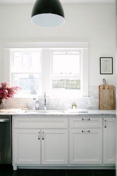 Inondée de lumière, cette petite cuisine vintage se paie un comptoir et un dosseret en marbre. Et cela lui va si bien.