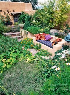 Susan Blevins of Taos, New Mexico, created an elaborate home garden featuring containers, perennial beds, a Japanese themed path and a regional style that reflects the Spanish and pueblo architecture of the area.  Colorful pillows add yet another dash of color to a bench in a sunken niche.