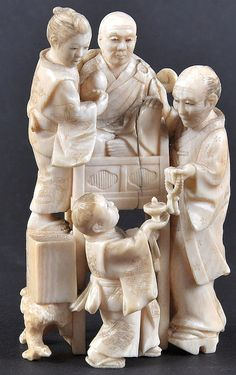 A LATE 19TH CENTURY JAPANESE MEIJI PERIOD IVORY OKIMONO depicting figures beside a male. Split. Signed. 3.5ins high.