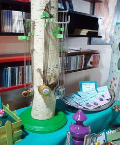 A birch branch with a painted wooden base and hooks for hanging necklaces.