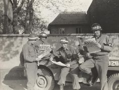 "Four MPs take a break along a German road to read in the ""Stars and Stripes"" newspaper about the Nazi surrender."