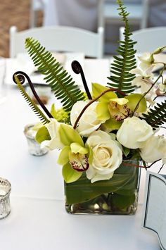 fiddle & reg. ferns with orchids & white roses... corn stalk leaves inside vase - wedding centerpieces