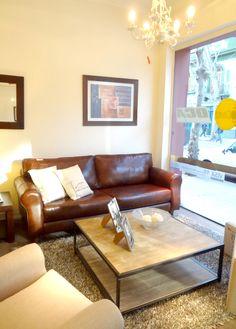 Nuestra vidriera con mesa de centro de madera y hierro, sófa de 3 cuerpos de cuero natural y butaca piazza. Arriba araña blanca.