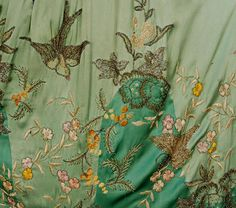 BEADED and EMBROIDERED SILK EVENING CAPE, 1920's. Two shades of green satin embroidered in pastel chenille and silk with gold metallic threads, having bronze seed and crystal bugle beads, and sequins in an undulating pattern of flowers, swallows and butterflies, with panne velvet lining and ruched collar. - Detail 3