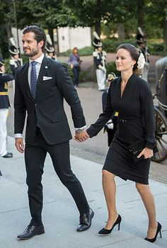 arrived on the arm of her husband Prince Carl Philip, nailed business chic in a black dress and leather belt. She brightened up her look with a stunning hair accessory – a white flower pinned into her elegant chignon.