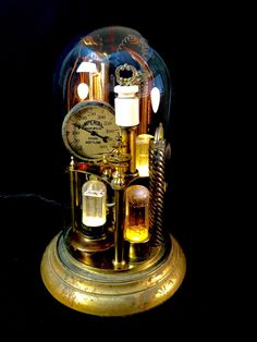 Tubes, hoses, gauges and pipes...under glass!  This steampunk inspired creation is the amalgamation of many different found objects from my immense collection of odds and ends.  Under this reclaimed glass dome are vintage radio tubes illuminated by LED bulbs and other illuminated curious artifacts. All lights are controlled by a rotary switch mounted in the base outside the glass dome. Theres a medium base dimmer socket in which a tubular Edison bulb is installed. The brightness of the…
