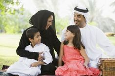 A Middle Eastern family sitting in a park