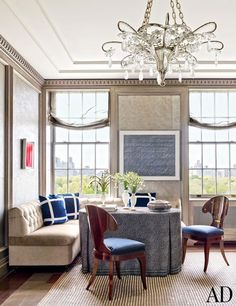 In one corner of the dining room, a Lucio Fontana painting (left) and a Cy Twombly work hang above a tufted banquette; the chandelier is 1940s French, and the tablecloth is made of a Lee Jofa fabric.