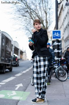 Womenswear Street Style by Ángel Robles. Elisa Nalin wearing checked wide-leg pants, sneakers and black blazer at Givenchy show, Paris. Fashion Photography from Paris Fashion Week.