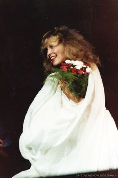 Stevie, beautiful in white, holding a floral bouquet      ~  ☆♥❤♥☆  ~             at the end of a concert during Fleetwood Mac's 'Mirage' tour, 1982
