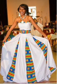 This ethnic inspired sleeveless and strapless wedding gown has kente trim around upper bust, waist, sides, and back of dress skirt with attached chapel train.  Lined with netting underneath. Zipper in back. The white veil has blue satin trim and kente headband included (at request of the customer). Kente purse sold separate. This wedding gown is made in the U.S.A. Kente is hand woven in Ghana.