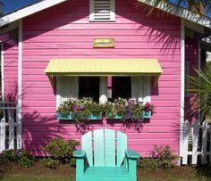 pink house, yellow awning, aqua chair