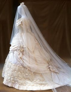 1860s wedding dress suitable for an imperial wedding in the cathedral. 18 meters of pure Italian silk taffetas were used to make this dream dress. The bodice is doubled with canvas and with bones. the neck is richly decorated with ribbon, flowers and beads and lace. The very wide