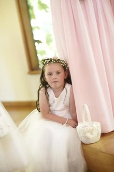 Flower girl wearing a custom designed silk flower crown. Featuring baby's breath and mini pink rose buds in a full crown.