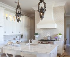 Stunning kitchen with antique lanterns pendants, creamy white kitchen cabinets & kitchen island with marble countertops, sink in kitchen island, white counter stools with gray leather cushions & silver nailhead trim, tan walls paint color and ivory subway tiles backsplash.