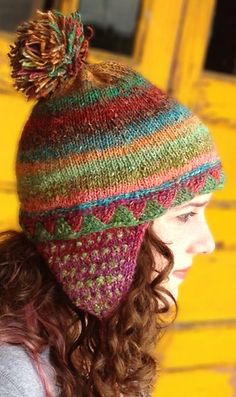 Free Knitting Pattern for Attention Span Hat - This colorful earflap hat by Mimi Kezer is a great sampler of knitting techniques. Pattern includes a pinhole cast-on, a bit of Entrelac, a lateral braid or two, some stranded colorwork, tassels and a pom-pom, German short rows, and a little stockinette stitch.