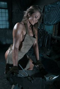 blacksmith student , well at least she has the apron on and is wearing gloves. Does ANYONE know where I can fine one of these for my Blacksmith shop?!?!?! I REALLY want one!!!!