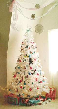 White Christmas tree with pretty ornaments. Love the doilies hung from the ceiling.