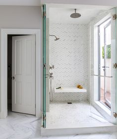 A white marble herringbone tiled bathroom floor leads to a walk in shower features walls clad in white and gray herringbone tiles lined with a white floating shower bench alongside a marble grid shower floor finished with seamless glass folding shower doors.
