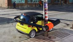 """To promote the wisdom of owning a tiny car in a big city, the global ad agency BBDO took a literal approach to advertising the Smart Fortwo in downtown Toronto with enormous bike locks, showing the ease of traveling within the city. In another nearby campaign, the company wedged a giant shoehorn behind the car, which was parked in a tiny space between two sedans. The slogan? """"Fits into tight places."""""""
