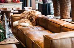 Old leather couch and sheep skin throw.