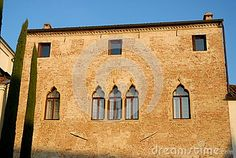 Photo made at the elegant villa where the pastor lives of Casalserugo a town in the province of Padua in the Veneto (Italy). In the image of the brick facade of a beautiful light colored, facing west, illuminated by the setting sun and framed by blue sky, the villa with windows, in particular, reveal the architecture of Venice, appear left too thin cypresses which also serve as the border with the adjacent church.
