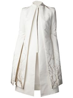 White cotton blend coat from Gareth Pugh featuring a mandarin collar, layered design throughout, and hem with sleeve metallic tree embroidered details throughout. Has long wide sleeves with underarm slit cuffs, front gunmetal-tone zip up fastening, and back inverted pleats. Is fully lined.