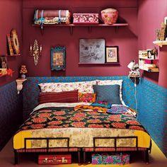 chambre de style kitsch-ethnique avec lits indiens, soubassement fait de feuilles de papier chinois à fleurs sur fond bleu, partie supérieure du mur couleur prune