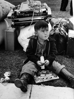 """Tagged for evacuation"": A Japanese American boy waits to be relocated to an internment camp wearing an identification tag to avoid being separated from his family. Russell Lee 1942 [3666x4896]"
