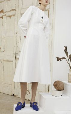 White double-faced cotton dress with button front detail and voluminous sleeves. Back zip closure with side pockets. Fitted at the waist with a-line shaped skirt and lined skirt by Rejina Pyo. The Vogue Edit.