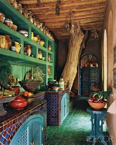 I like all sorts of things about this room, the green of the shelves, the blue tiling, the herringbone floor, the tree in the house, the shade of blue paint, the archway, the exposed beams... love