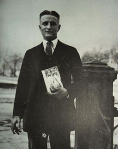 F. Scott Fitzgerald standing with a copy of The Great Gatsby, 1925