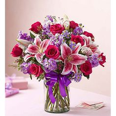 This gorgeous bouquet will capture her #heart faster than Cupid can shoot his arrows! #Romantic red #roses mingle with deep purple stock, monte casino and statice inside a dazzling purple glass vase.